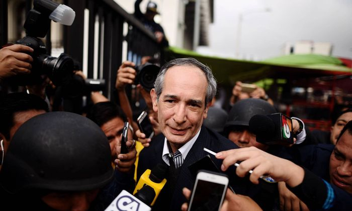 Guatemalan former President Alvaro Colom C delivers remarks to press as he is escorted after being