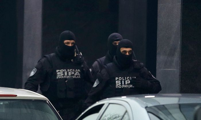 Members of Bosnia´s State Investigation and Protection Agency stand outside the buliding of Dnevni Avaz newspaper in Sarajevo