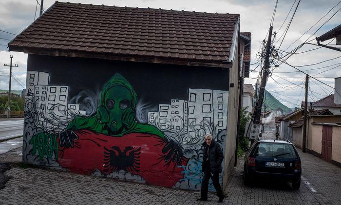 Ein Mann in Mitrovica, Kosovo, spaziert an einem Graffito im albanischen Süden der Stadt vorbei.