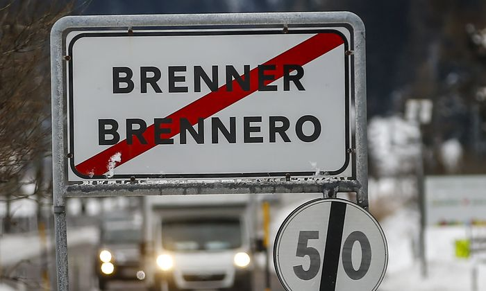 Cars drive along a street with a sign reading ´Brenner-Brennero´ in the Italian village of Brenner on the Italian-Austrian border