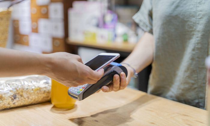 Customer paying cashless with smartphone in a shop model released Symbolfoto property released PUBLI