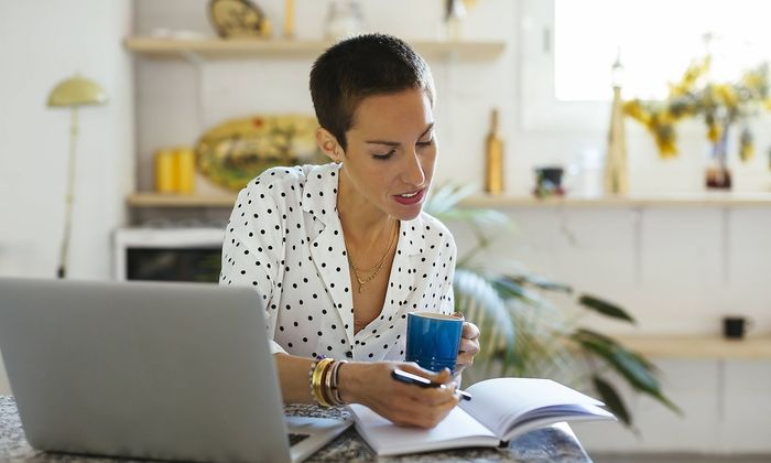 Woman drinking coffee and using laptop and notebook on table model released Symbolfoto property rele