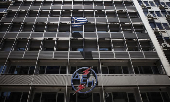 A Greek national flag flutters at the PPC headquarters building in Athens
