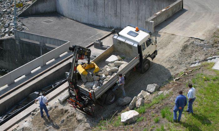 Baustellenfahrzeug mit Granitsteinen beladen