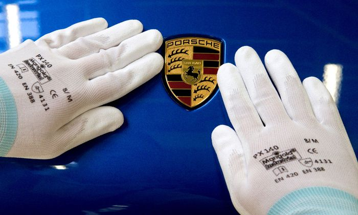 FILE PHOTO: A man does the final touches on the Porsche logo of a Macan at the plant in Leipzig