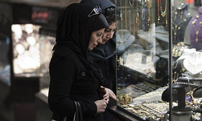 Women look at jewellery at a shop window in a bazaar in northern Tehran