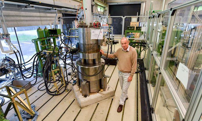 Institutsleiter Rudolf Scheidl vor einem Versuchsaufbau, an dem die Hydraulik von Walzwerken studiert wird.