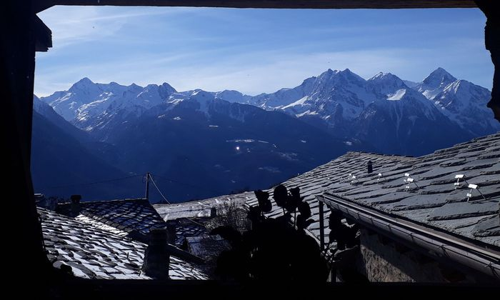 Ein Blick über die charakteristischen Walser-Häuser mit steingedeckten Dächern. Die Viertausender sind zum Greifen nah.