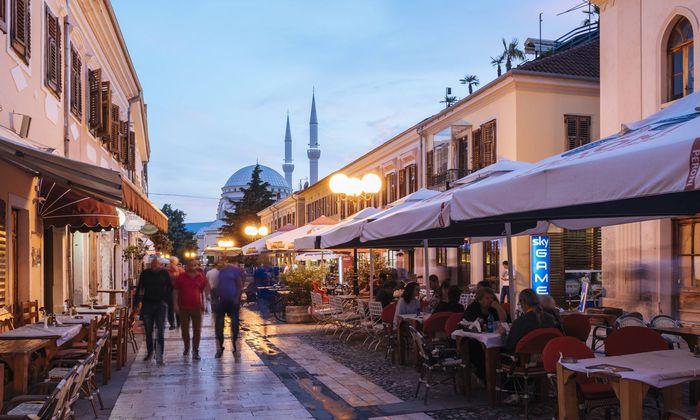 Auf der Rruga Kol Idromeno flaniert und diniert abends die ganze Stadt, im Hintergrund die al-Zamil-Moschee. Luftbild von Shkodra im Drina-Tal.