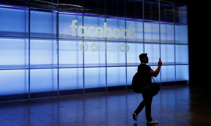 An attendee takes a photograph of a sign during Facebook Inc's F8 developers conference in San Jose