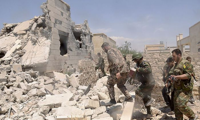 Forces loyal to Syria's President Assad carry their weapons during an operation in Aleppo