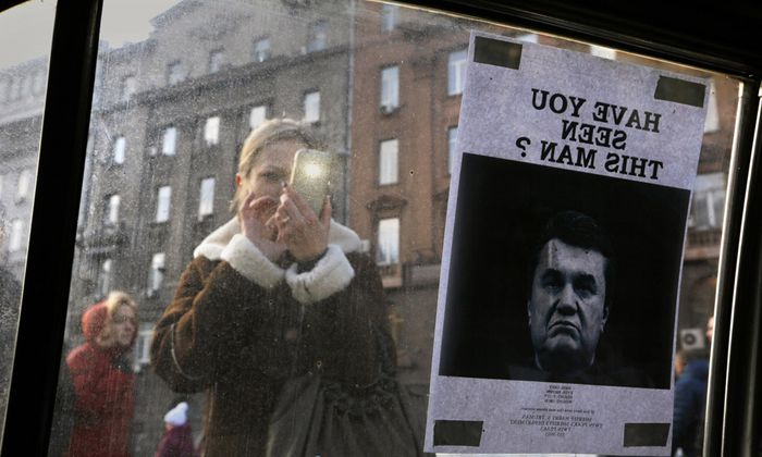 A woman takes photos of a ´Wanted´ notice for fugitive Ukrainian President Yanukovich near Kiev´s Independent Square