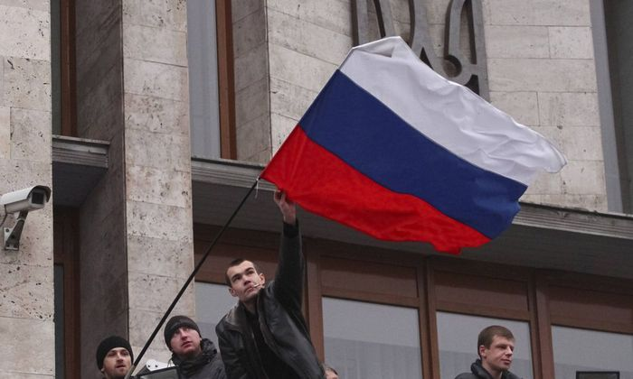 Pro-Russian demonstrators erect a Russian flag outside the regional government building in Donetsk