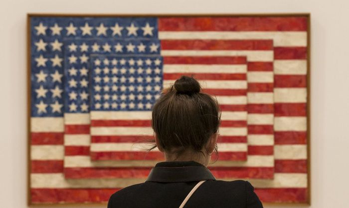 A woman looks at 'Three Flags' by Jasper Johns during the opening preview at The Whitney Museum of American Art in New York