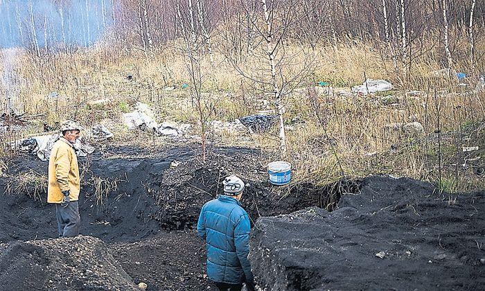 in der blauen Jacke – steht vor einem Abgang in einen alten Schacht. Im Hintergrund: die Ruinen eines Bergwerksgebäudes in der Nähe der Stadt Wałbrzych.