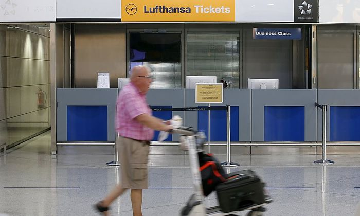 A man pushes his trolley past Lufthansa desk at Athens airport