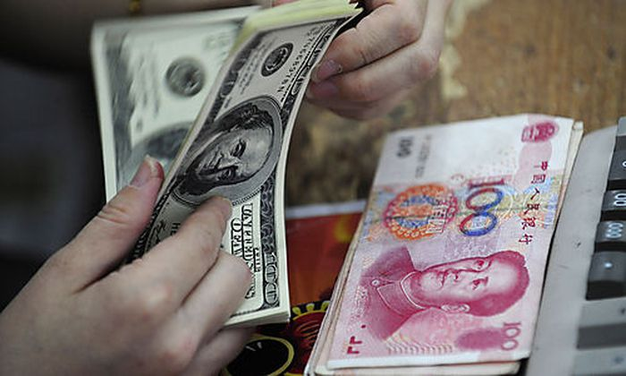 A Chinese clerk counts U.S. dollars in exchange for the Chinese renminbi at a bank in Hefei in centra