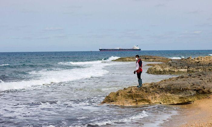 Ein Mann hält an der Libyschen Küste Ausschau nach Leichen, die angespült werden.