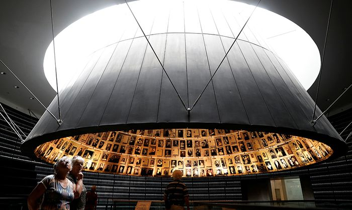 People look at pictures of Jews killed in the Holocaust during a visit to the Hall of Names in the Holocaust History Museum at the Yad Vashem World Holocaust Remembrance Center in Jerusalem, as Israel´s annual Holocaust Remembrance Day begins tonight
