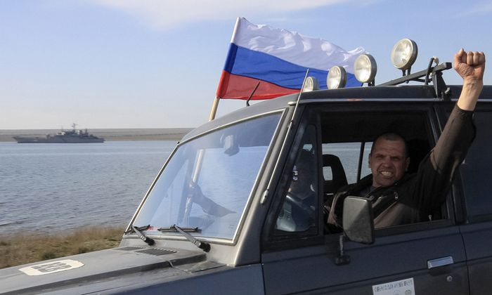 A member of a pro-Russian self defence unit gestures as he drives past the Ukrainian naval landing vessel ´Konstantin Olshansky´ in Donuzlav bay in Crimea