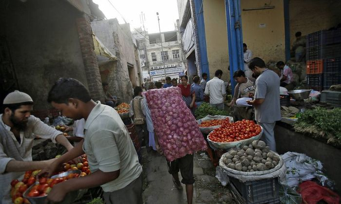 A labourer carries a sack of onions at a wholesale vegetable market in the old quarters of Delhi