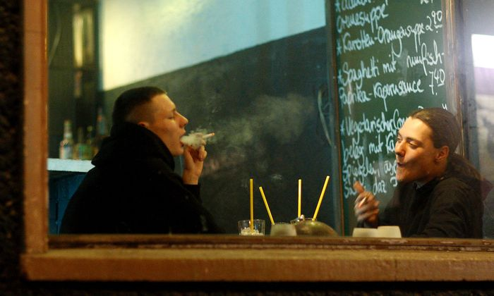 Two men smoke cigarettes inside a pub in Berlin