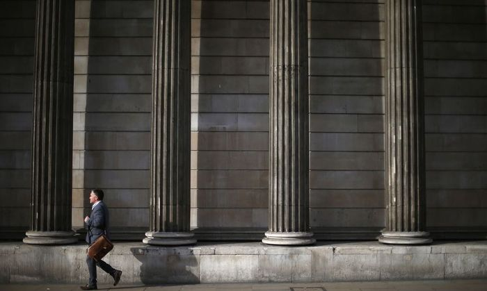 A man walks past the columns of the Bank of England in the city of London