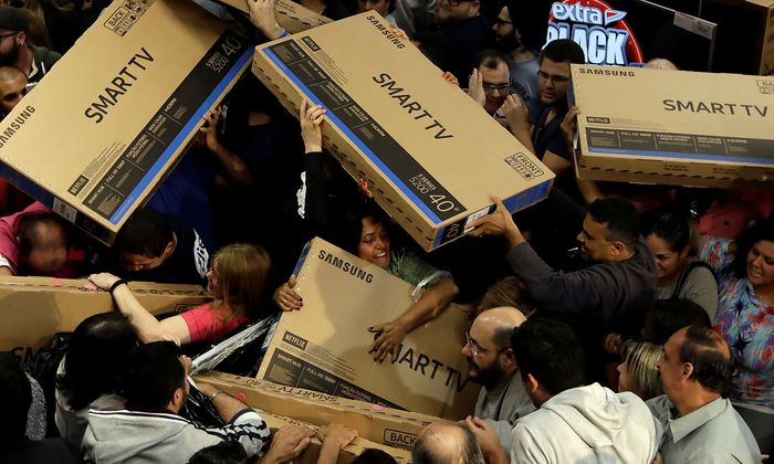 Shoppers reach out for television sets as they compete to purchase retail items on Black Friday at a store in Sao Paulo