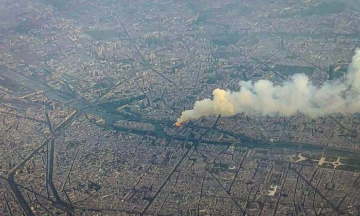 Ein Bild der Ile de la Cité und der brennenden Kathedrale Notre-Dame, das ein Flugzeug-Passagier im Vorbeiflug geschossen hat.