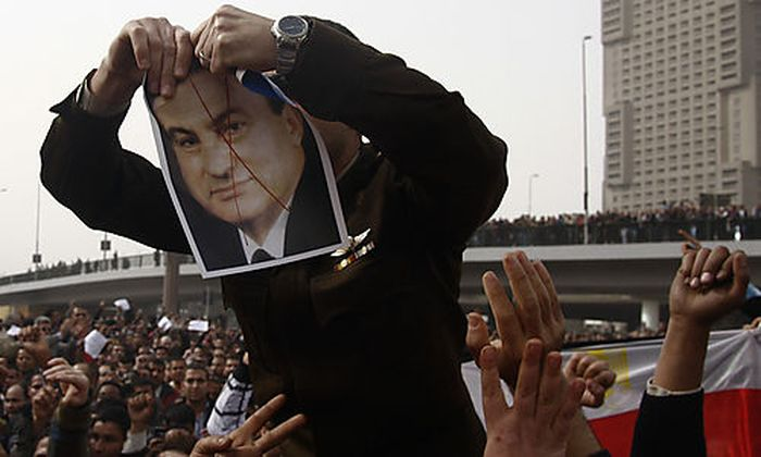 An army officer who joined anti-government protester tears up a picture of Egyptian President Hosni M