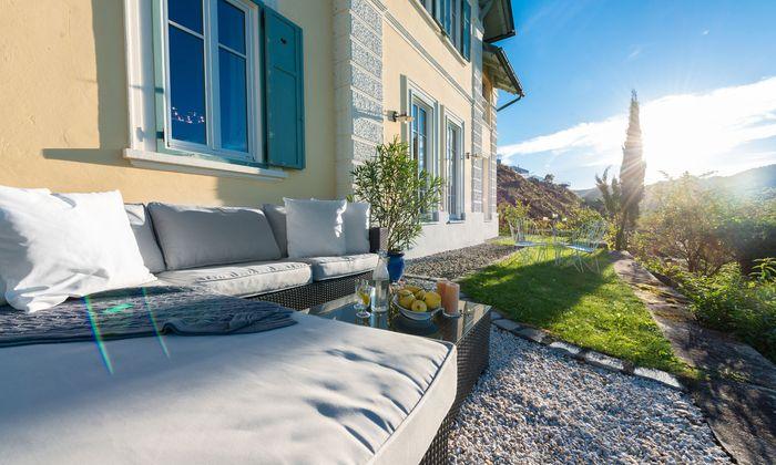 Reifnitz: In Kaisergelb mit grünen Fensterläden sitzt die Jahrhundertwendevilla auf einem kleinen Hügel mit Blick über den Wörthersee.
