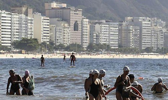 Residents collect garbage on Copacabana beach in Rio de Janeiro