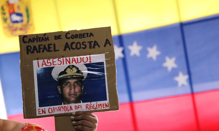 A woman shows a placard with a picture of Rafael Acosta, after a news conference in Caracas