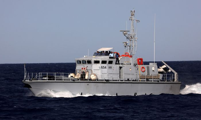 A Libyan coast guard vessel powers next to former fishing trawler Golf Azzurro of the Proactiva Open Arms rescue charity in the Western Mediterranean Sea