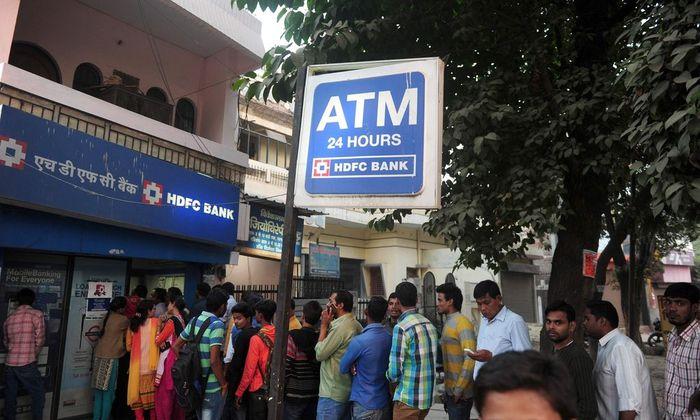 Während immer mehr Geschäfte verwaisen, drängen sich in Indien vor Banken und Bankomaten immer mehr Menschen.