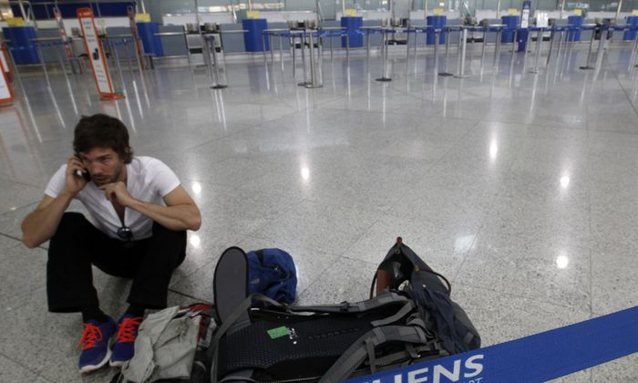 A passenger sits inside an empty hall at the Athens Eleftherios Venizelos airport during a 24-hour labour strike in Athens