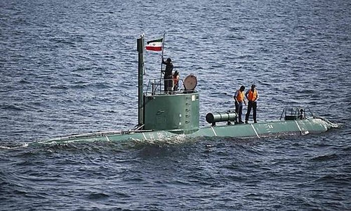Military personnel place a flag on a submarine during the Velayat-90 war games by the Iranian navy in