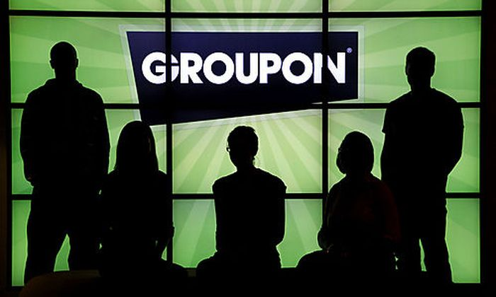 FILE - In this Sept. 22, 2011 file photo, employees at Groupon pose in silhouette with the company lo