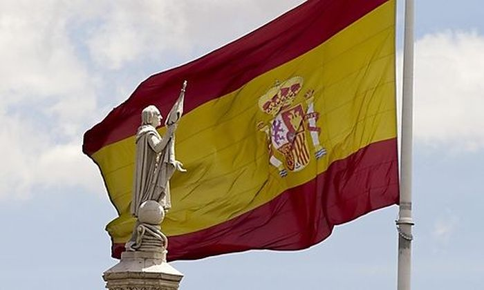 A statue of Christopher Columbus with an extended hand is seen in front of a Spanish flag in central