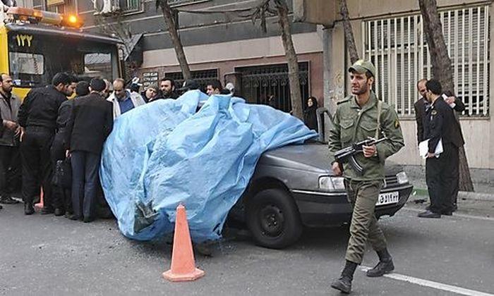 A policeman walks past the car belonging to Iranian nuclear scientist Mostafa Ahmadi-Roshan at a blas