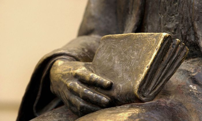 Hand einer Statue mit Buch