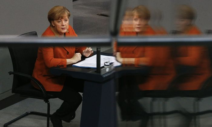 German Chancellor Merkel is reflected in glass fence at German Bundestag in Berlin
