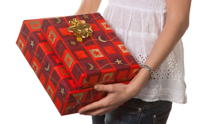 Young woman hinding a christmas present