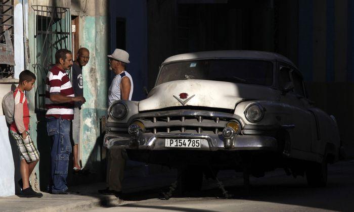 Cubans talk near a broken car in Havana