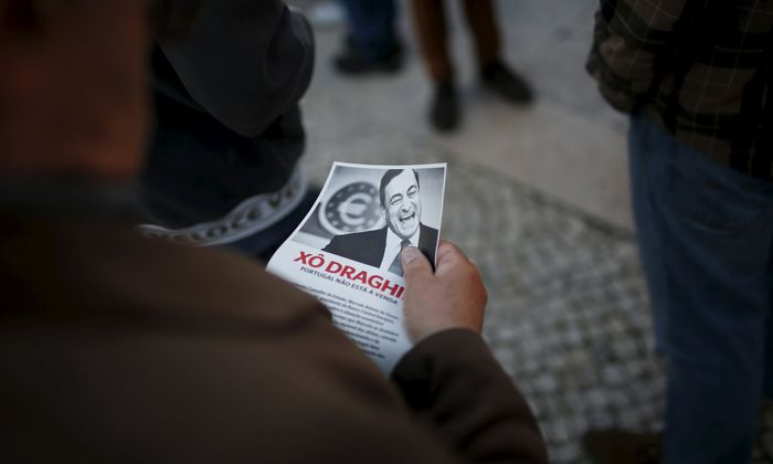 A demonstrator reads a pamphlet during a protest against the visit of European Central Bank (ECB) President Mario Draghi in Lisbon