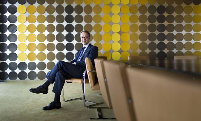Jens Weidmann Praesident der Deutschen Bundesbank sitzt vor einer Wandverkleidung von Victor Vasa