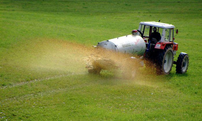 Traktor faehrt auf einem Feld und duengt