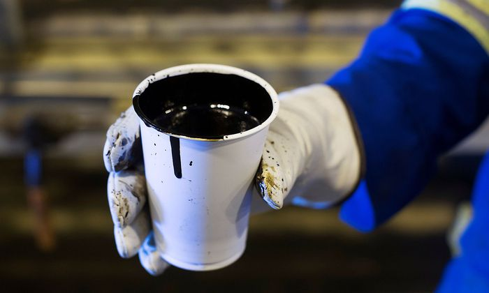 FILE PHOTO: A worker holds a cup of heavy oil south of Fort McMurray