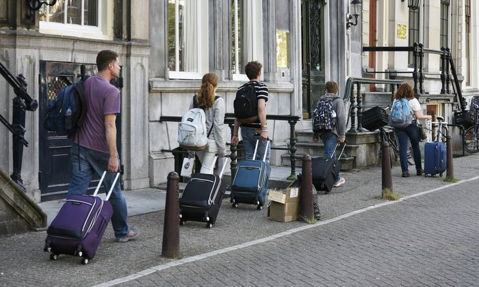 The Netherlands Amsterdam June 2018 Airbnb tourists with suitcases walk through the center of Am