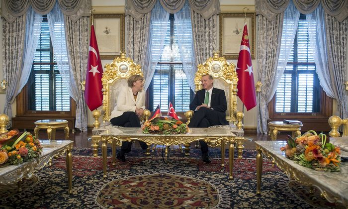 Handout shows Turkish President Erdogan listening to German Chancellor Merkel during their meeting in Istanbul